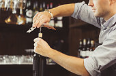 Bartender concentrated on uncork of elite drink at bar counter. Male sommelier open wine bottle with corkscrew. Waiter with bottle of alcohol beverage and bottle-screw in hands.