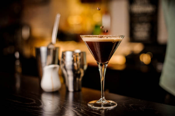 bartender decorated espresso cocktail drink white foam coffee bean classy bartender garnish martini espresso cocktail drink foam coffee bean on top bar counter martini stock pictures, royalty-free photos & images