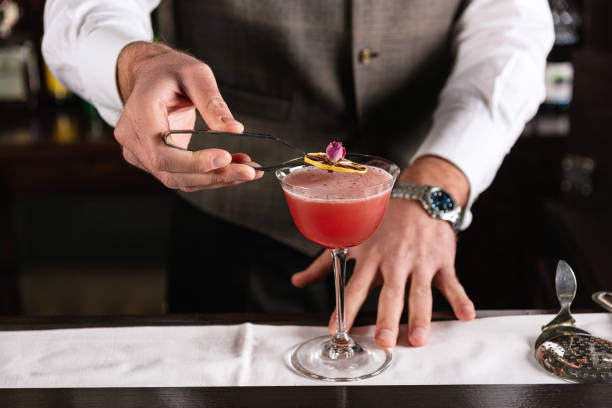 Bartender decorating alcohol cocktail with a rose flower and slice of lemon stock photo