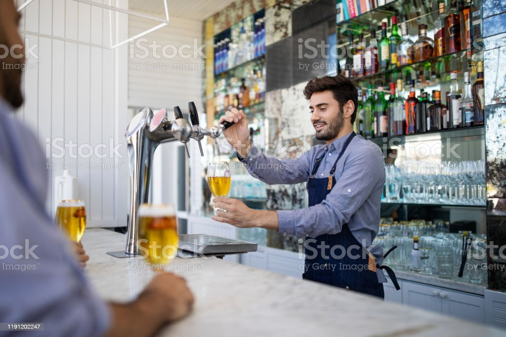 Bartender filing beer in a glass from tap - Royalty-free Adult Stock Photo