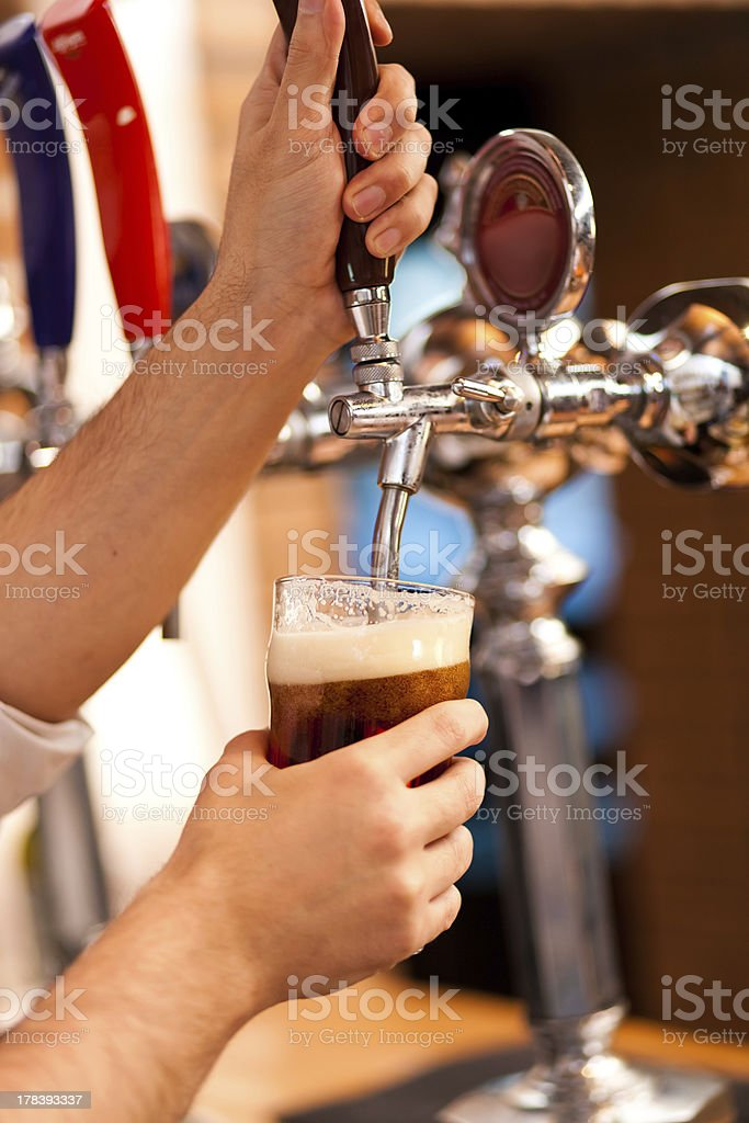 Bartender filling a glass with beer royalty-free stock photo