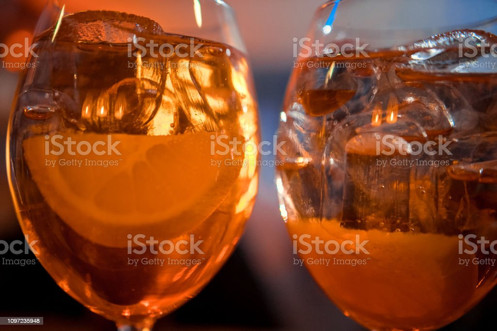 Bartender garnishing on the counter three Aperol Spritz, a classic refreshing Italian aperitif made mixing Aperol, Prosecco and sparkling soda to enjoy with friends and family at the bar before meals. stock photo