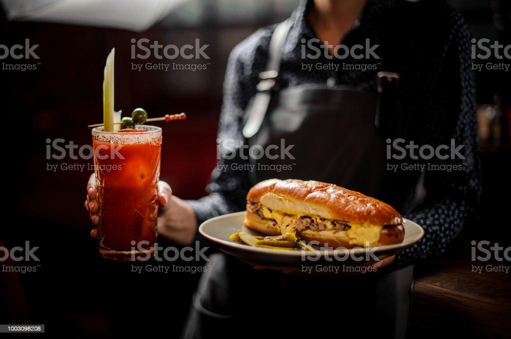Garota de barman, segurando o sanduíche com carne e vermelho verão coquetel - foto de acervo