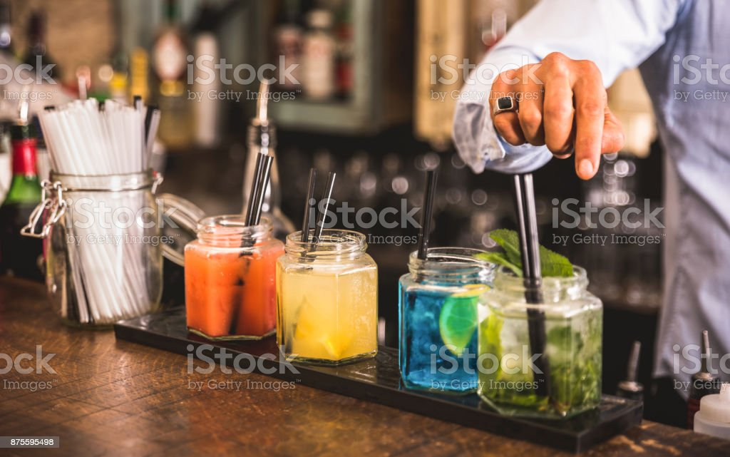 Bartender hand at multicolored fashion drink with straw on vintage glass cups in fashion cocktail bar - Food and beverage concept with professional barman working at mixology restaurant - Vivid colors royalty-free stock photo