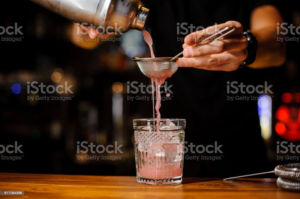 Bartender hand pouring pink cocktail drink in bar stock photo