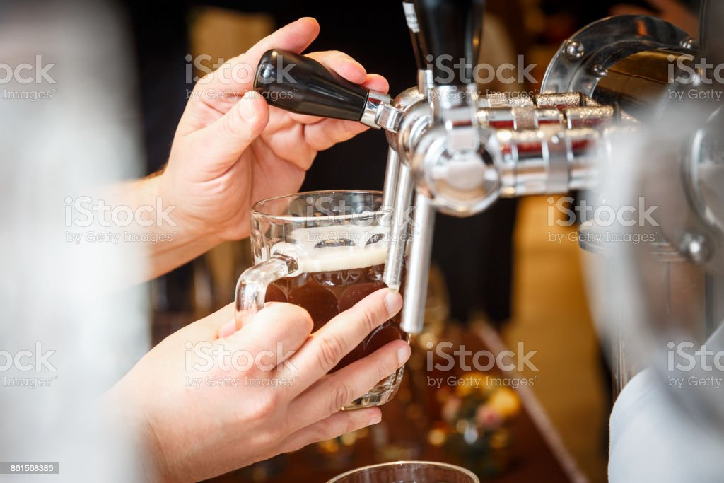 bartender hands pouring a draught craft beer stock photo