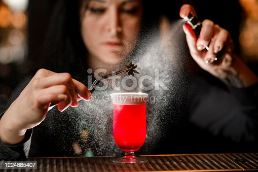 Professional bartender hold by hand tweezer with aniseed over glass with red alcoholic drink and spraying on it.
