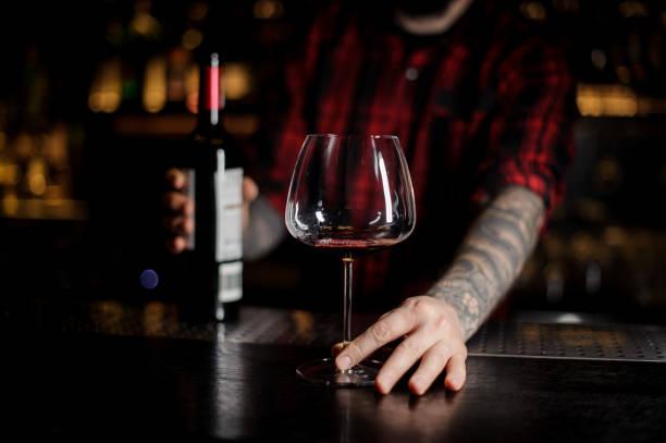 barkeeper hält eine flasche und glas rotwein - dekorierte schnapsflaschen stock-fotos und bilder