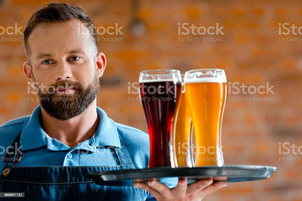 Bartender holding serving tray with glasses of beer Bearded bartender holding serving tray with glasses of beer 25-29 Years Stock Photo