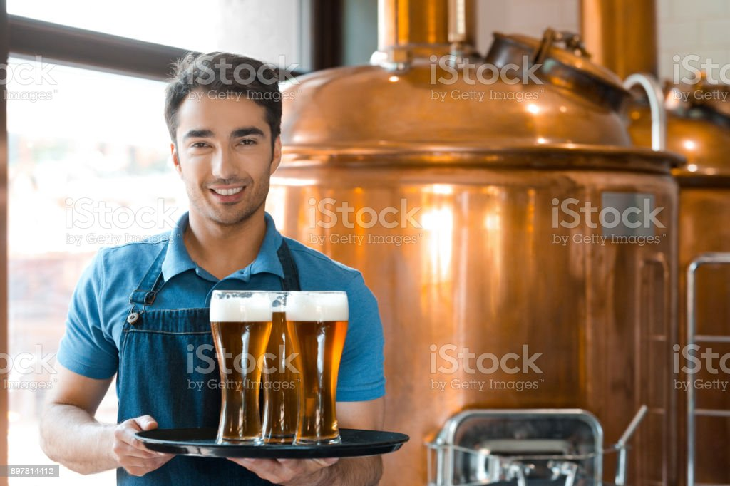 Bartender holding serving tray with glasses of beer Portrait of happy young male bartender holding serving tray with glasses of beer in micro brewery Adult Stock Photo