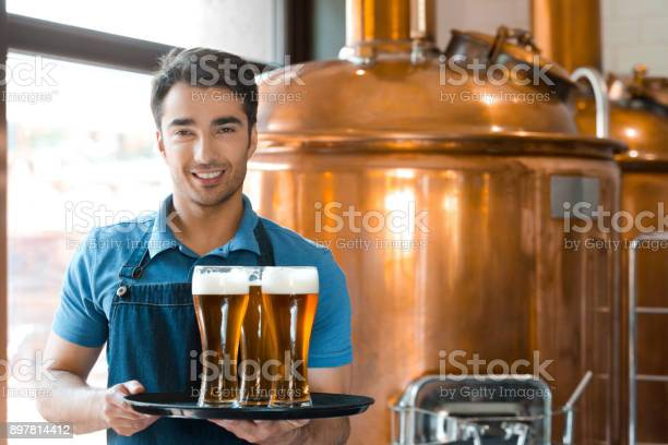 Bartender Holding Serving Tray With Glasses Of Beer Stock Photo - Download Image Now