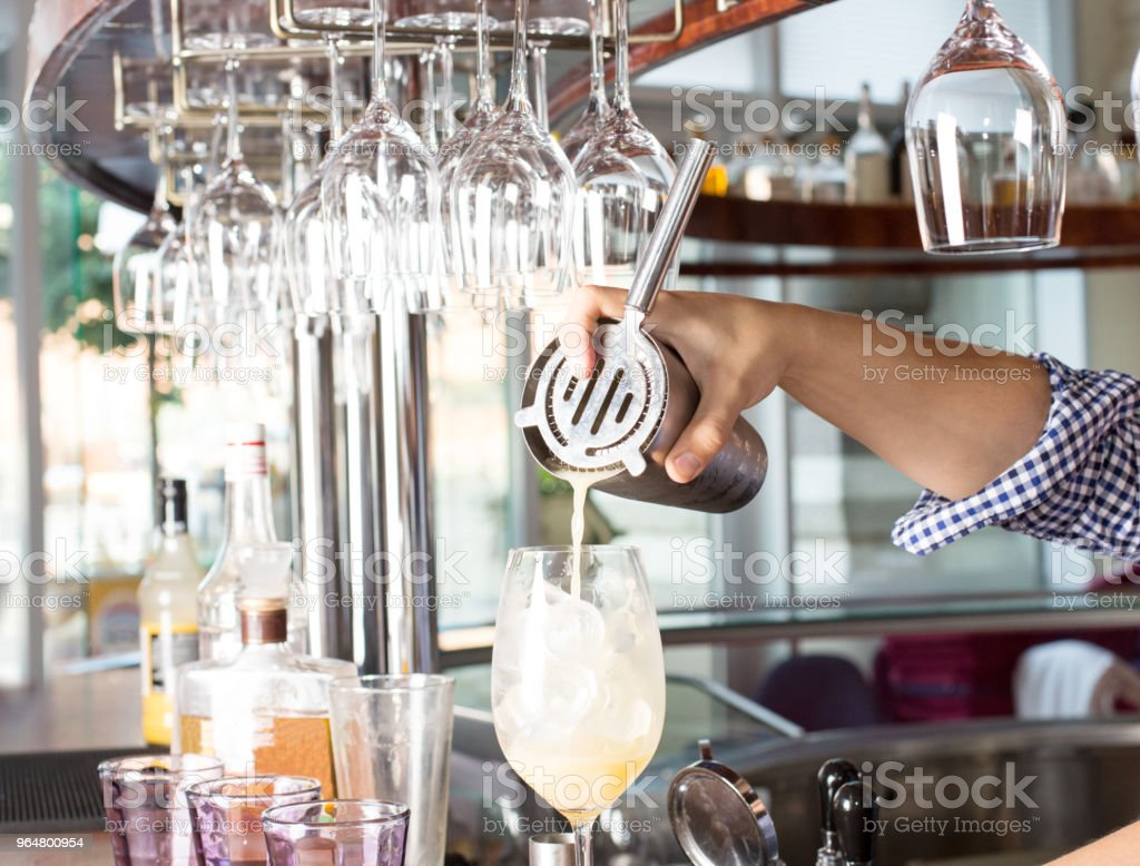 Bartender holding steel shaker up and pouring mixed drink into t royalty-free stock photo
