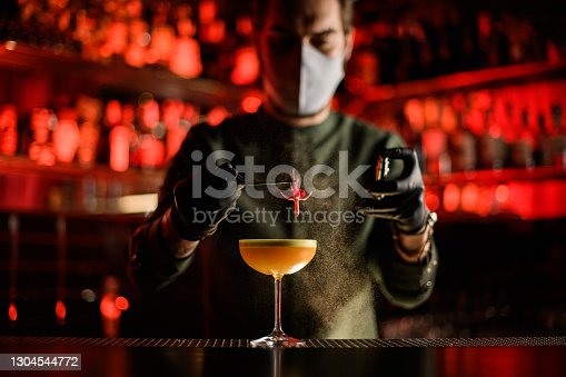 bartender in mask and gloves holds pink flower with tweezers over glass of cocktail and sprinkles on it