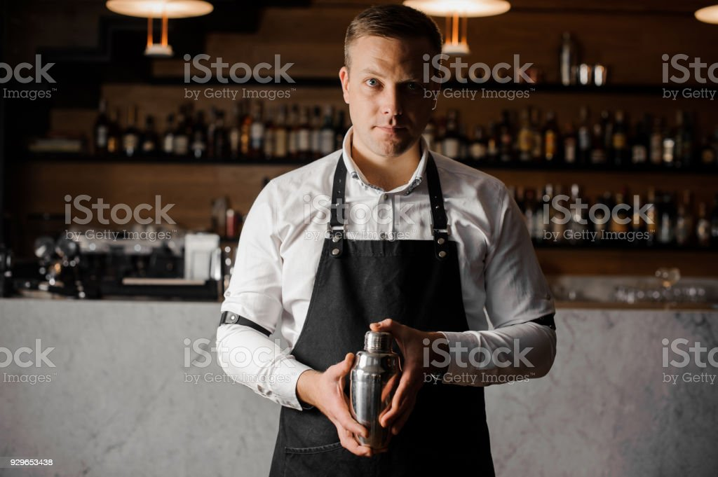 Bartender in white shirt and apron holding a shaker against the bar counter stock photo