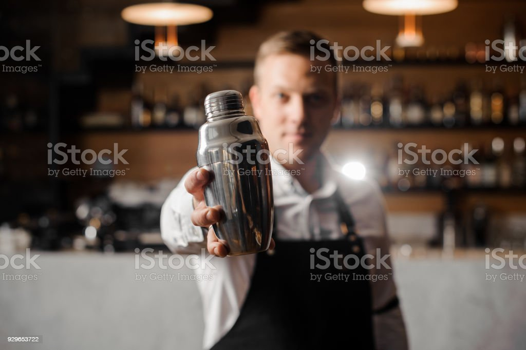 Bartender in white shirt and apron holding a shaker stock photo