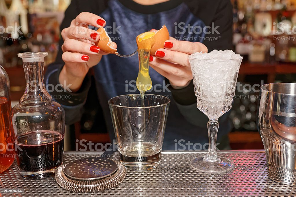 Bartender is adding egg white to the glass stock photo