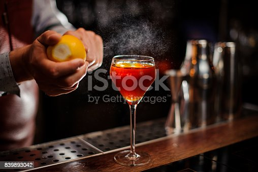 istock Bartender is adding lemon zest to the cocktail at bar counter 839893042