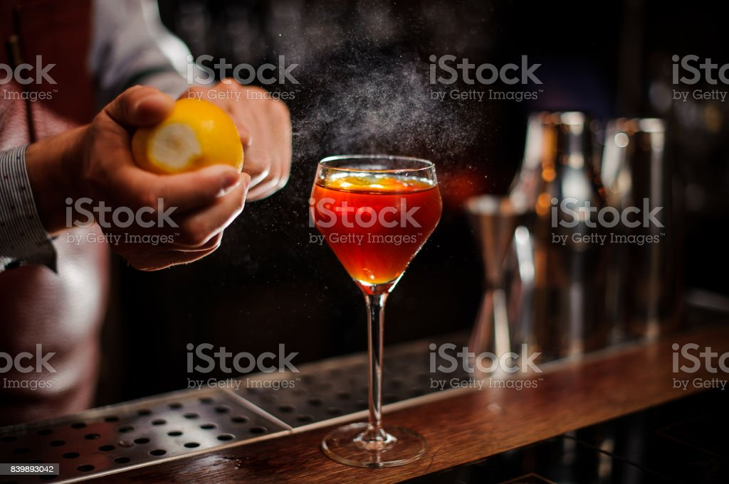 Bartender is adding lemon zest to the cocktail at bar counter стоковое фото