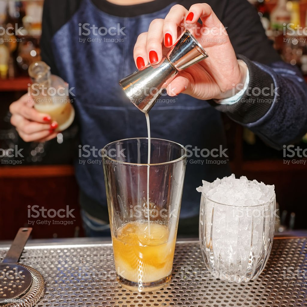 Bartender is adding milk liqueur to the shaker stock photo