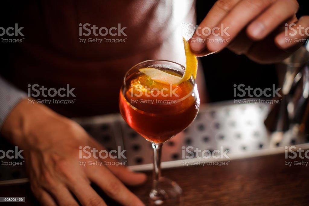 Barkeeper ist einen Cocktail mit Zitronenschale dekorieren. – Foto