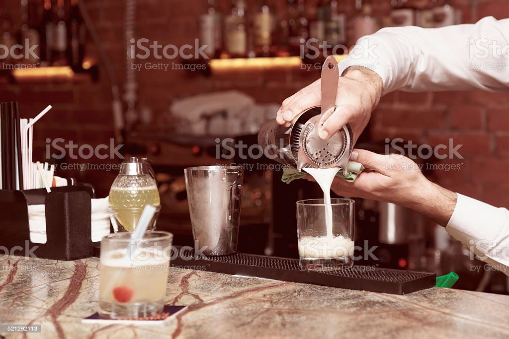 Bartender is making a cocktail, toned image stock photo