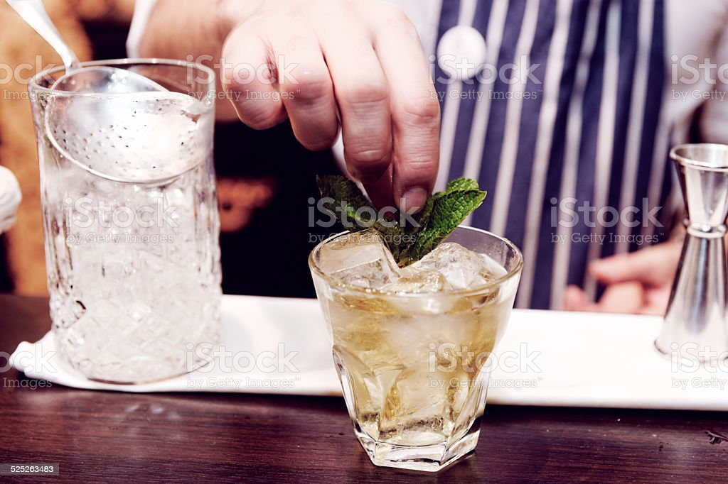 Bartender is making cocktail at bar counter, toned stock photo