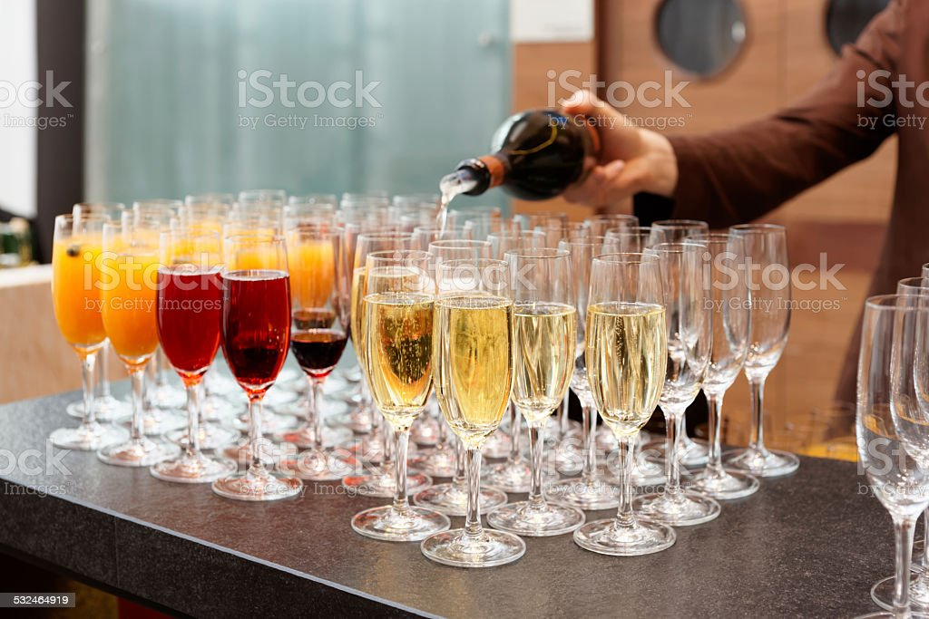 Bartender is pouring sparkling wine in glasses stock photo