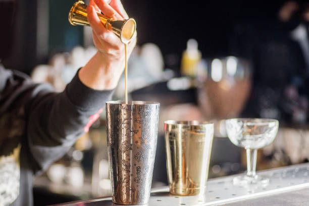 bartender is preparing a cocktail. Bartender pours a cocktail stock photo