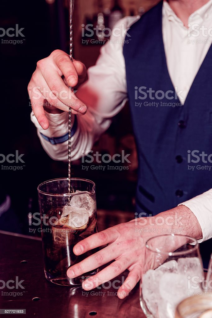 Bartender is stirring cocktail on bar counter, toned stock photo