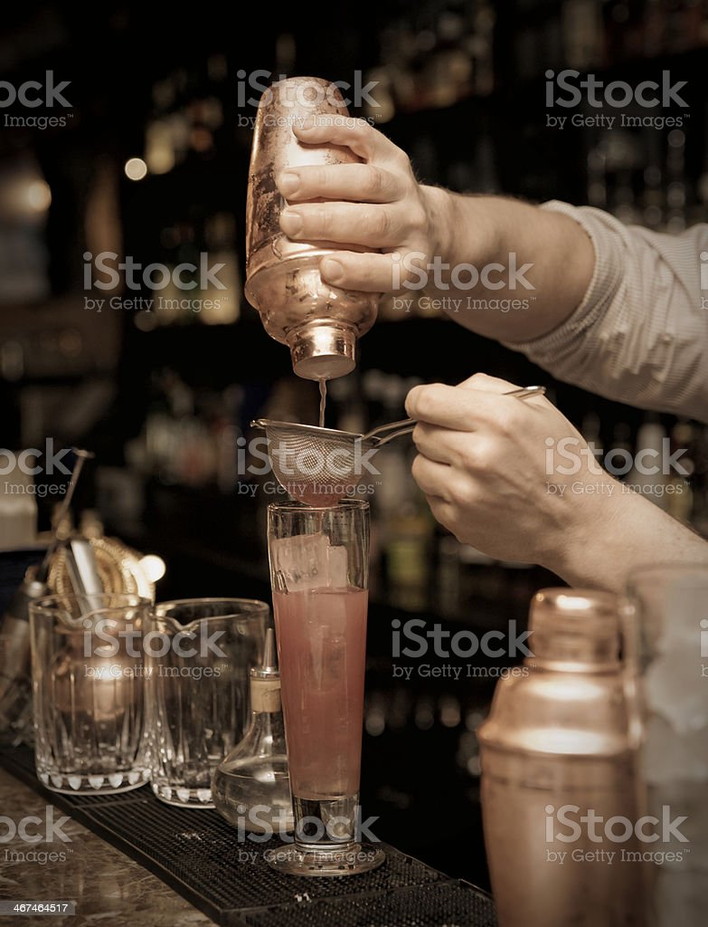 Bartender is straining cocktail stock photo