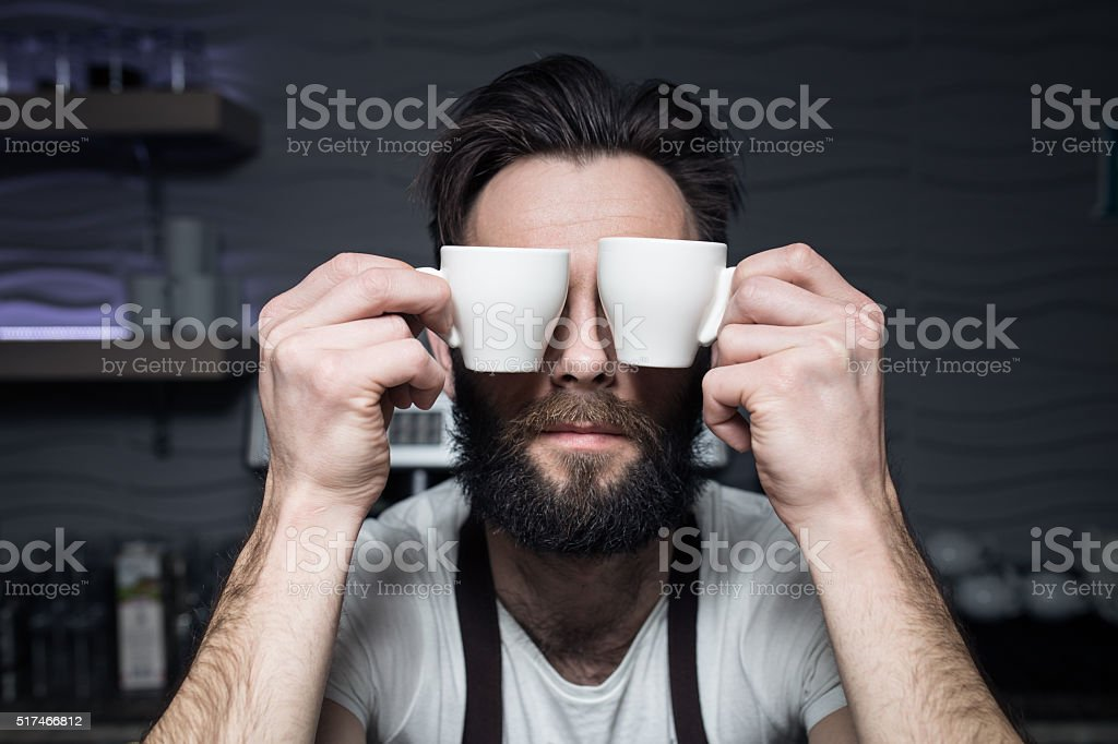 bartender keeps cups of coffee near face; stock photo