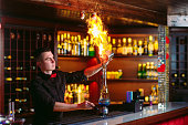 Bartender makes hot cocktail in a restaurant in the bar