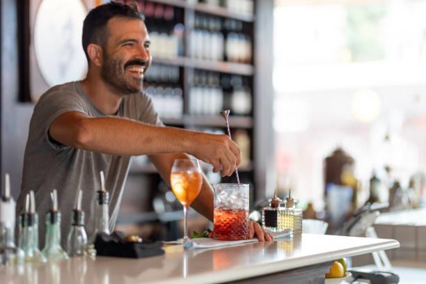 Bartender Making Cocktails Bartender Making Cocktails in Australian bar bartender stock pictures, royalty-free photos & images