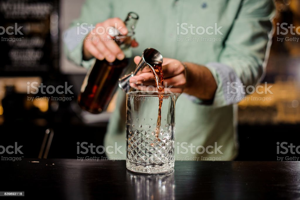 Bartender making red alcoholic cocktail , metal jigger and bar environment stock photo