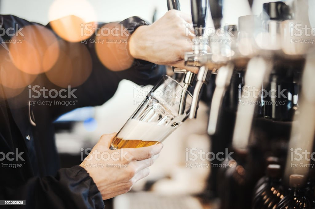 Bartender man poors glass of beer. stock photo