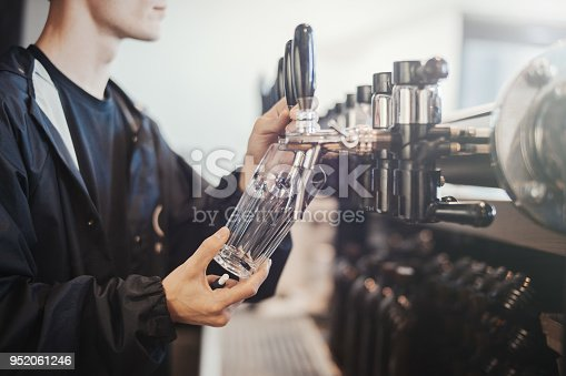Bartender man poors glass of beer. Glass and hands are on background and focus, bar faucets are blurred.