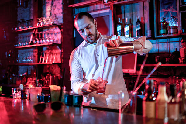 Bartender mixing a cocktail Bartender in white shirt pouring a cocktail into glass. bartender stock pictures, royalty-free photos & images
