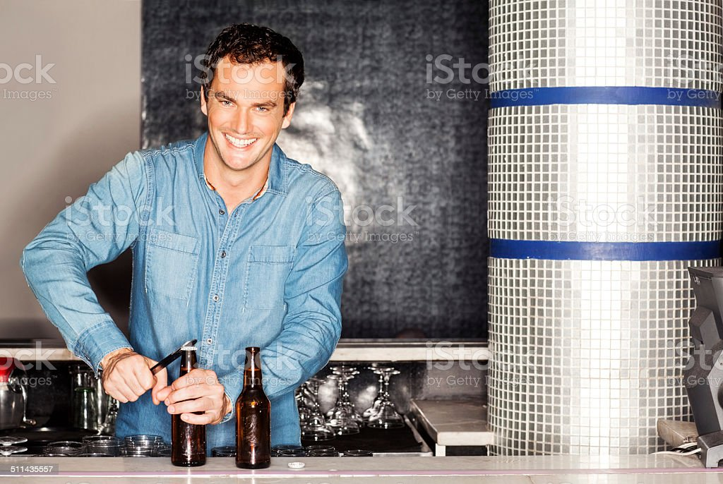 Bartender Opening Beer Bottle At Counter In Nightclub stock photo