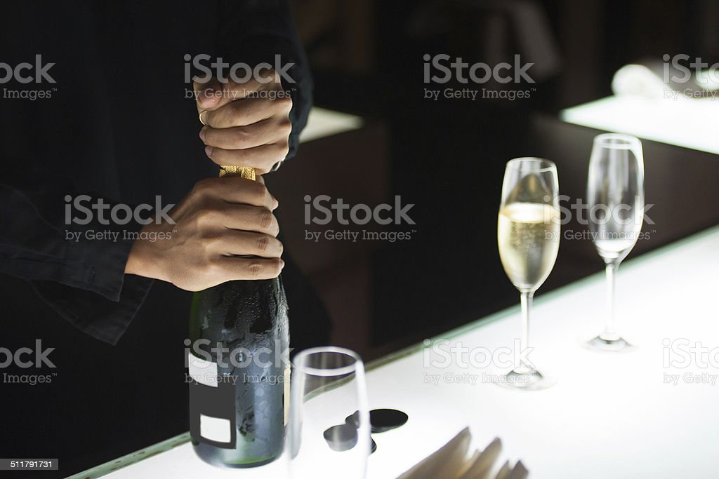 Bartender opening champagne bottle stock photo
