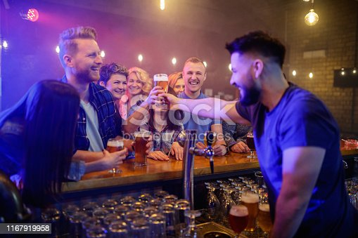 Bartender passing a glass of beer over the counter to smiling woman in cheerful company