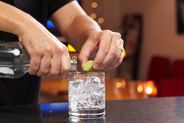 Bartender Hands squeezing lime and pouring gin or vodka into lowball glass with seltzer or tonic.  Professionally shot, color corrected, exported 16 bit depth, retouched and saved for maximum image quality.  vodka stock pictures, royalty-free photos & images