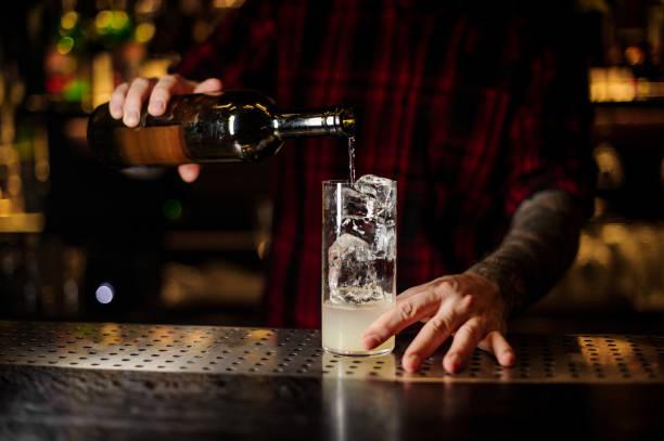 barkeeper gießen einen alkohol aus der flasche, so dass cocktail trinken - dekorierte schnapsflaschen stock-fotos und bilder
