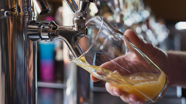 Bartender pouring a beer from the tap - foto stock