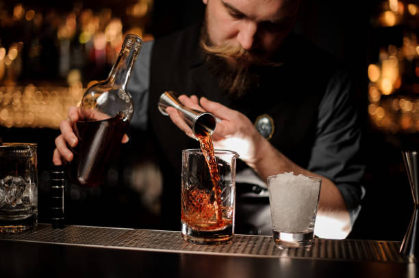 Bartender pouring a brown alcohol to the cocktail from the steel jigger Bartender pouring a brown alcohol to the cocktail from the steel jigger to a glass on the bar counter on the blurred background pallet jack stock pictures, royalty-free photos & images