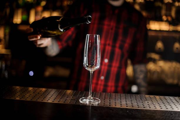 barkeeper einen champagner aus der flasche in ein glas gießen - dekorierte schnapsflaschen stock-fotos und bilder