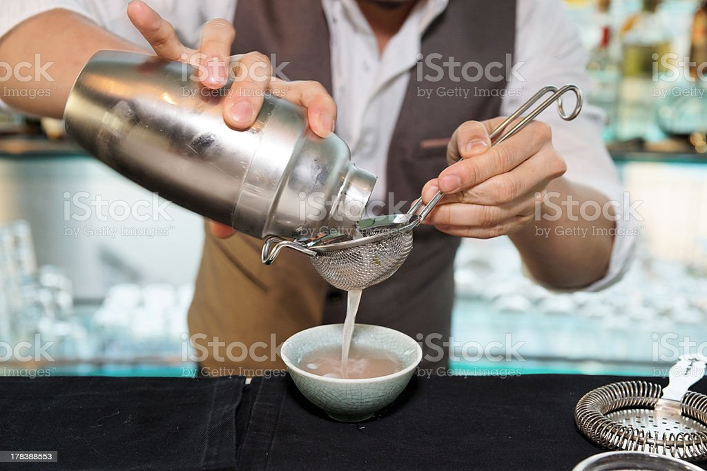Bartender pouring a cocktail through a sieve royalty-free stock photo