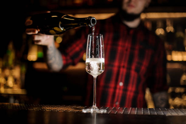 barkeeper einen köstlichen champagner aus der flasche in ein glas gießen - dekorierte schnapsflaschen stock-fotos und bilder