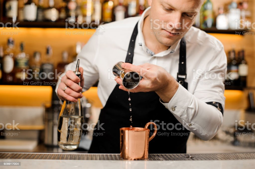 Bartender pouring a portion of alcoholic drink into the cup stock photo