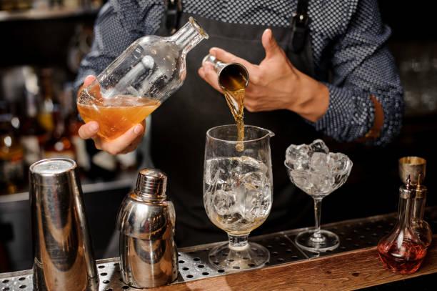 barkeeper einen teil des sirups in großen cocktailglas gießen - dekorierte schnapsflaschen stock-fotos und bilder