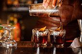 グラスに酒を注ぐバーテンダー